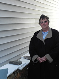 Linda Metzger stands next to her damaged wall