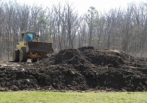 The recipient of several dump; truck loads of topsoil is busily levelling his new yard.